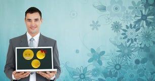 Portrait of businessman holding laptop against floral patterned background. Digital composite of Portrait of businessman holding laptop against floral patterned Stock Photos
