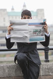 Portrait of a businessman holding newspaper in front of his face with St. Paul's Cathedral in the background Royalty Free Stock Photo