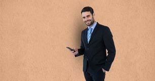 Portrait of businessman holding smart phone over beige background Royalty Free Stock Photos