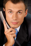 Portrait of businessman holding telephone receiver Stock Image