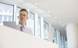 Portrait of businessman with laptop and documents at railing Royalty Free Stock Photos