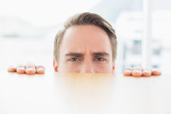 Portrait of businessman looking over blurred wall at office Stock Image