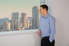 Portrait of businessman. Man look out the window. Portrait of businessman. Man look to the window to skyscrapers Royalty Free Stock Photography