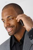 Portrait of businessman with mobile phone. Closeup portrait of Afro-American businessman talking on mobile phone, smiling Stock Image
