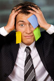 Portrait of businessman in office with blank adhesive notes stuck to his face Royalty Free Stock Photography