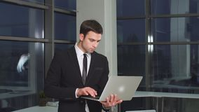 Portrait of businessman in office with laptop computer. stock video footage