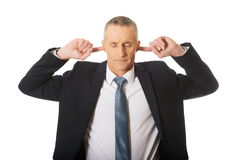 Portrait of businessman plugging his ears Stock Photos