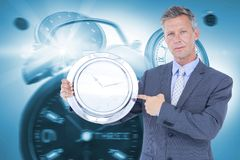 Composite image of portrait of businessman pointing at wall clock Royalty Free Stock Photos