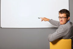 Portrait of businessman pointing at whiteboard and making face in office Royalty Free Stock Image