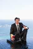 Portrait of a businessman posing with a cocktail on a briefcase Royalty Free Stock Image