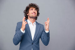 Portrait of a businessman praying with crossed fingers. Over gray background and looking up Stock Photo