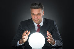 Portrait Of Businessman Predicting Future With Crystal Ball. On Desk Stock Photo