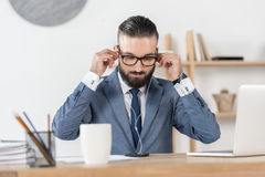 Businessman putting earphones into ears at workplace in office Royalty Free Stock Image