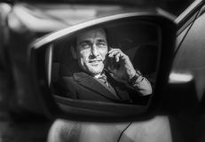 Portrait of a businessman in the rearview mirror of car, day, outdoor stock photos