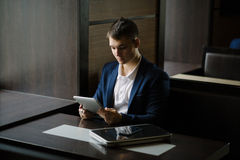 Portrait of businessman seeing on his tablet pc in cafe Royalty Free Stock Images