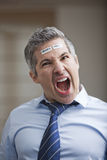 Portrait of a businessman shouting with barcode on forehead Stock Photography