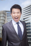Portrait of Businessman Shouting and Looking At Camera, Buildings in the Background Stock Photo