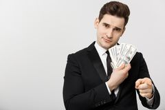 Portrait of businessman showing money and pointing fingers isolated over white background.  Royalty Free Stock Photo
