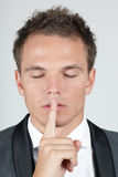 Portrait of businessman showing silence gesture Stock Photos