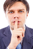 Portrait of businessman showing silence gesture with his forefin Stock Images
