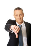 Portrait of businessman showing thumb down sign Stock Images