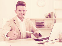 Portrait of businessman showing thumbs up in modern office Royalty Free Stock Photo