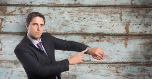 Portrait of businessman showing time on wristwatch against wooden wall Royalty Free Stock Image