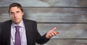 Portrait of businessman shrugging shoulders against wooden wall stock photography