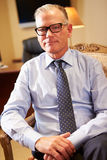 Portrait Of Businessman Sitting In Chair. Wearing Glasses Looking At Camera royalty free stock photos