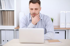 Portrait of businessman sitting at the desk in office workplace.  Royalty Free Stock Photo
