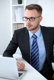 Portrait of businessman sitting at the desk in office workplace Stock Photography
