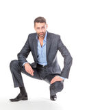 Portrait businessman sitting on his haunches Royalty Free Stock Image