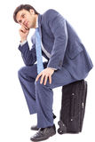 Portrait of a businessman sitting on his luggage Royalty Free Stock Photos