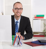 Portrait: Businessman sitting in his office with suit and tie. Royalty Free Stock Photo