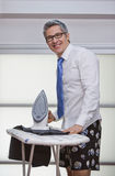Businessman smiling while ironing pants Royalty Free Stock Photos