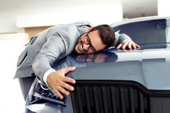 Portrait of a businessman smiling joyfully and embracing a new car at the dealership showroom stock image