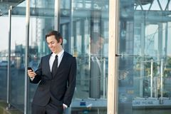 Portrait of a businessman smiling and looking at mobile phone outdoors. Close up portrait of a businessman smiling and looking at mobile phone outdoors Stock Photo
