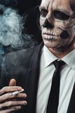 Portrait businessman smoking with makeup skeleton Royalty Free Stock Photo