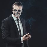 Portrait businessman smoking with makeup skeleton Stock Image