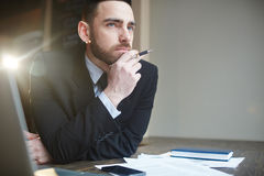 Portrait of Businessman Solving Problems. Portrait of modern successful businessman wearing black formal suit working in office with documentation, resting head Stock Images