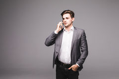 Portrait of a businessman speaking on cell phone isolated on a grey background Royalty Free Stock Images