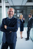 Portrait of businessman standing with arms crossed and colleagues talking in background Royalty Free Stock Image