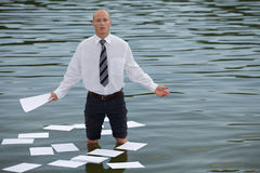 Portrait of businessman standing in lake with papers floating on water Royalty Free Stock Photo