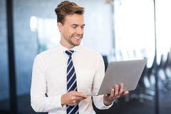 Portrait of businessman standing with a laptop in office. Portrait of businessman using a laptop in front conference room in office Royalty Free Stock Photography