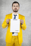 Portrait of a businessman in a suit holding a gold contract for royalty free stock photo