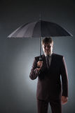 Portrait of businessman in suit under umbrella Royalty Free Stock Images
