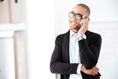 Portrait of businessman talking on the mobile phone. Portrait of a businessman talking on the mobile phone looking away in office Royalty Free Stock Photography
