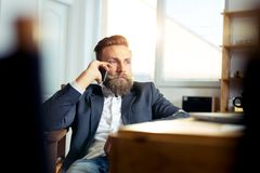 Portrait of businessman talking on mobile phone in office Royalty Free Stock Image