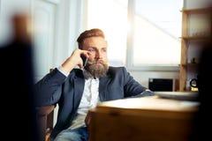 Portrait of businessman talking on mobile phone in office. Portrait of young  businessman talking on mobile phone in office Royalty Free Stock Image