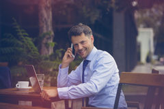 Portrait of businessman talking on mobile phone while using laptop Stock Image